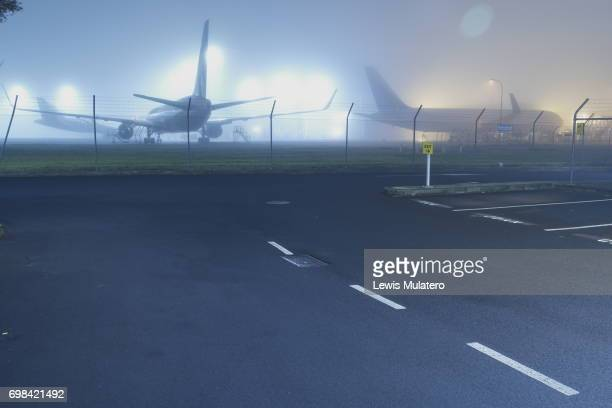 Night time empty airport carpark in front of grounded aircraft shrouded in fog