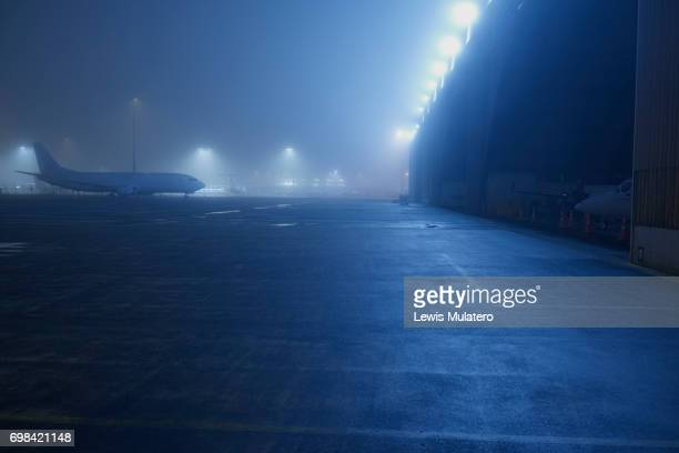 Night time grounded cargo aircraft shrouded in fog on tarmac next to aircraft hanger