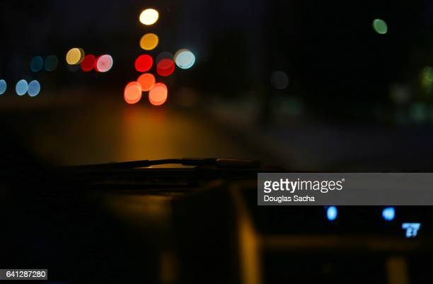 night time street life from a moving vehicle - dashboard camera point of view stock photos and pictures