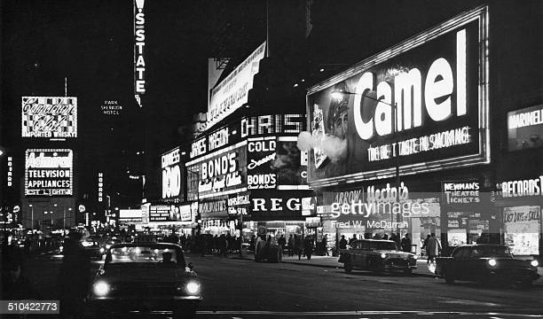 Night time view north along Broadway of Times Square New York New York February 21 1964 At right is a neon illuminated billboard for Camel cigarettes...