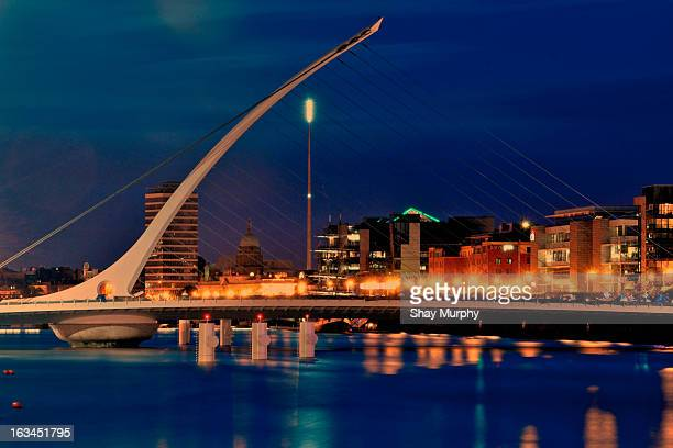 Night time view of Dublin city across the River Liffey with Samuel Beckett Bridge, Liberty Hall, and the Spire.