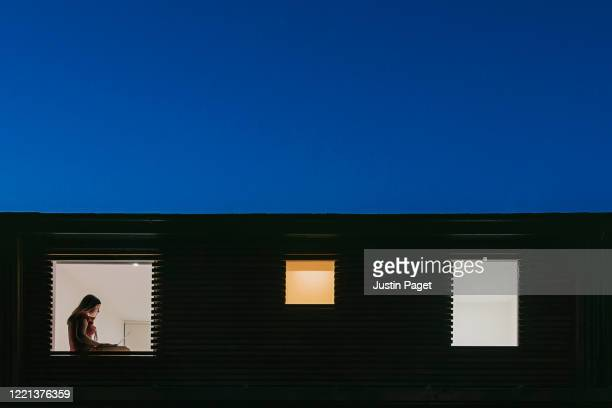 night time view of home exterior - figure on laptop in the window - quarantäne stock-fotos und bilder