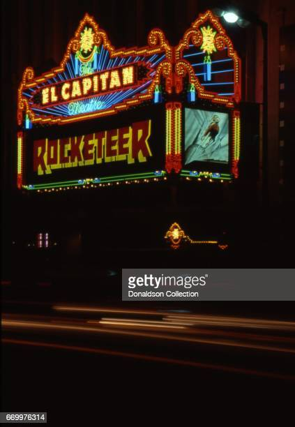 A night time view of the El Capitan Theater with the movie Rocketeer on the marquee and cars lights streaking by in January 1991 in Los Angeles...