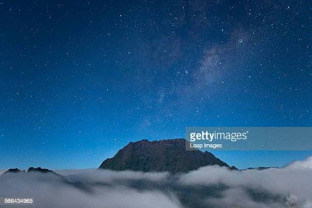 Night time view of the Piton des Neiges peak poking above the clouds on the French island of Reunion in the Indian Ocean
