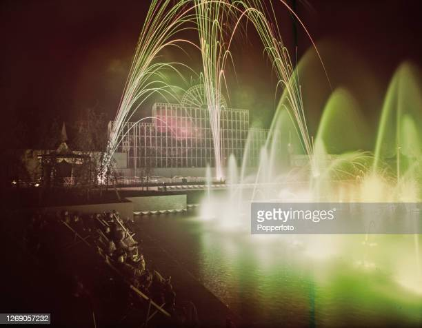 Night time view of visitors enjoying the illuminated fountains in the Battersea Pleasure Gardens created as part of the Festival of Britain...