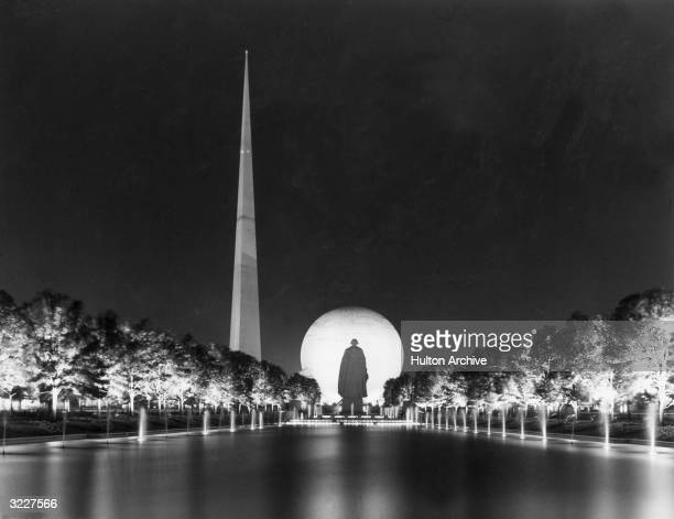 Night view at the World's Fair, Flushing Meadows, Queens, New York City. The pool, fountains, 'The Trylon' obelisk, the 'Perisphere' and statue of...