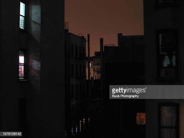 night view between tenement buildings in manhattan - fensterfront stock-fotos und bilder