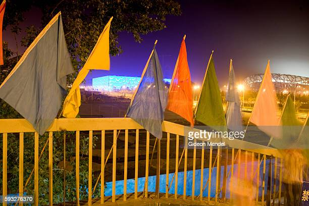 A night view from a pedestrian bridge decorated with flags of the Olympic Park which is still under construction The National Aquatics Centre and the...