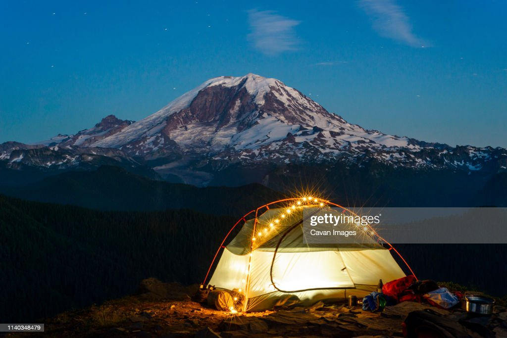 Night view of backpacking tent with string lights and Mt Rainier : Stock Photo