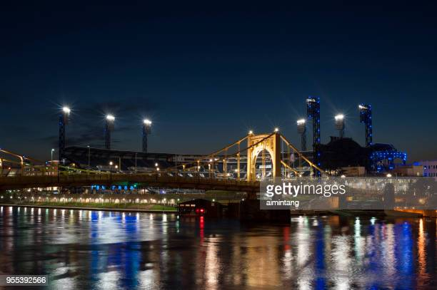 Night view of  bridge over Allegheny River with PNC Park in background in Pittsburgh
