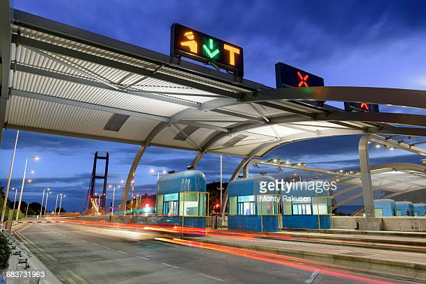 Night view of cars passing through toll booth at bridge