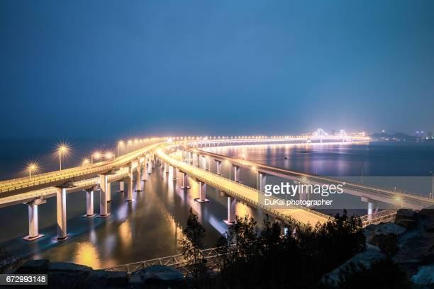 night view of dalian xinghai bay bridge - dalian stock photos and pictures