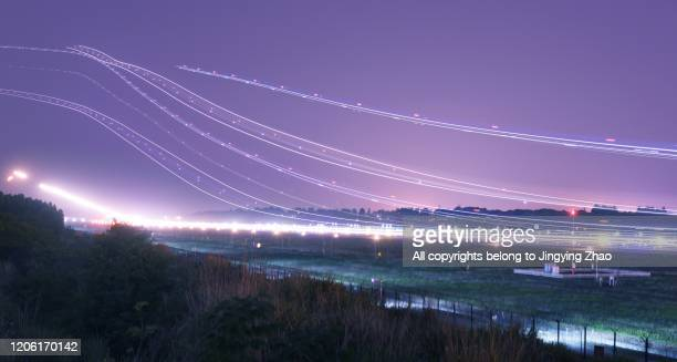 night view of dense light tracks of aircrafts flying in airport - igniting stock pictures, royalty-free photos & images