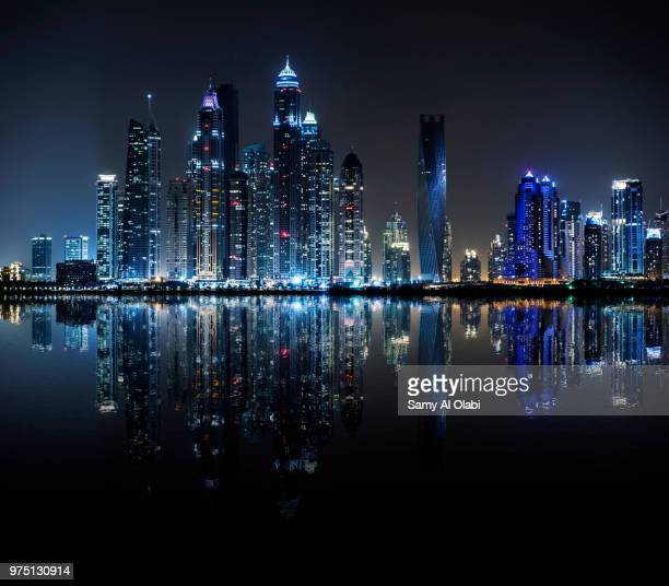 night view of dubai marina reflected in water, dubai, united arab emirates - dubai stockfoto's en -beelden
