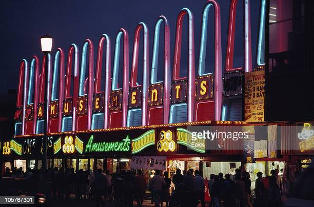 A night view of holiday makers walking along the Golden Mile which is illuminated by neon signs for amusements in the seaside town of Blackpool...