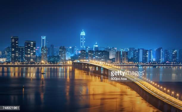 Night view of illuminated bridge and modern skyscrapers in background, Wenzhou, Zhejiang, China
