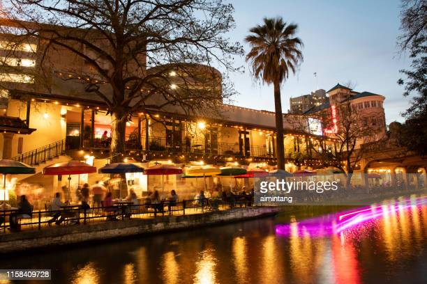 night view of river walk with people walking along the river banks or dining in restaurants in downtown san antonio - san antonio river walk stock pictures, royalty-free photos & images