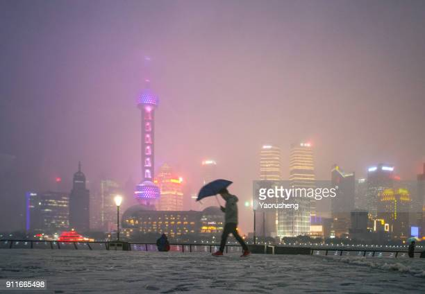 night view of shanghai in snowing,passenger passing the bund platform in the night - huangpu river stock photos and pictures