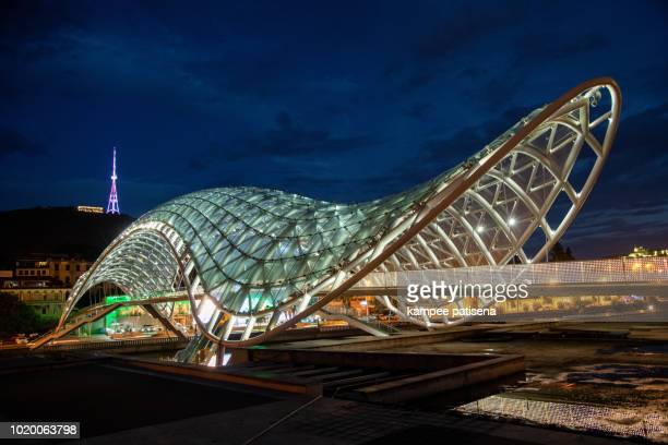"""night view of the """"bridge of peace"""" in tbilisi. georgia country - georgia country stock pictures, royalty-free photos & images"""