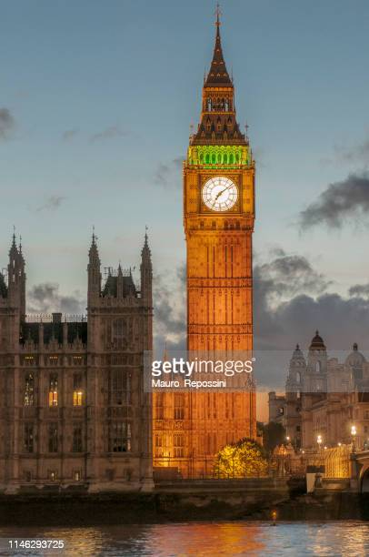 night view of the houses of parliament, the big ben and the thames river at the city of westminster, london, england, uk. - ora legale foto e immagini stock
