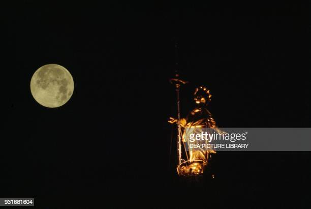 Night view of the Madonnina with the full moon in the background on the left by Giuseppe Perego and Giuseppe Bini gilded copper statue atop the...