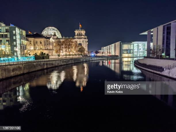 night view of the river spree with the reichstag building in the background in berlin, germany. - kuppel stock-fotos und bilder