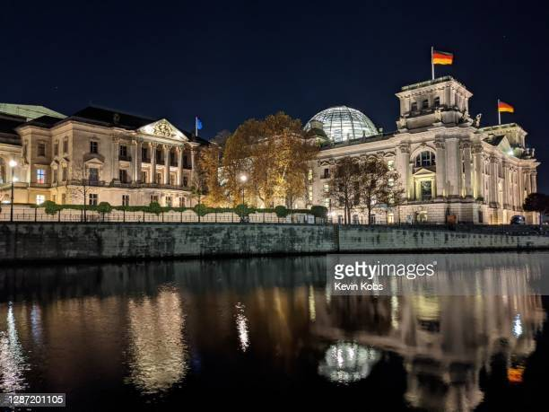 night view of the river spree with the reichstag building in the background in berlin, germany. - cupola stockfoto's en -beelden