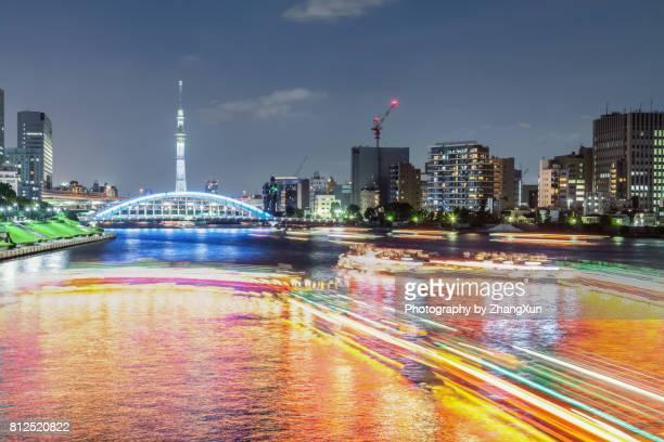 night view of tokyo cityscape with many house boats illuminated and eitai bridge, tokyo sky tree over sumida river in tsukishima aera, chuo ward, tokyo, japan. - 永代橋 ストックフォトと画像