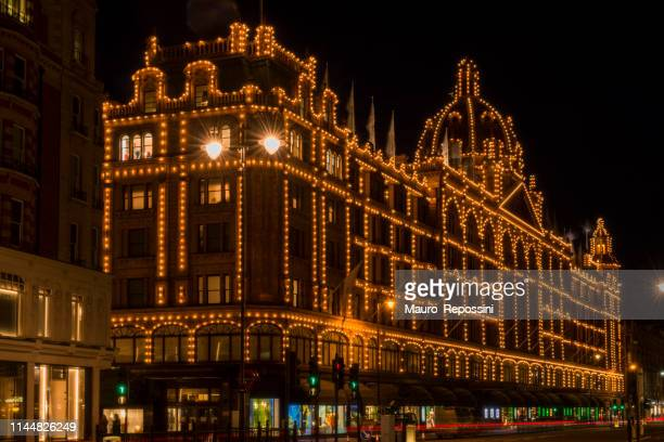 night view of unrecognizable people walking in the streets of the elegant knightsbridge district at london, england, uk. - knightsbridge stock pictures, royalty-free photos & images
