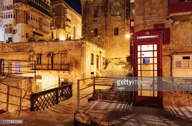 night view of victoria gate bridge with red phone box, in valletta old town, malta - red telephone box stock pictures, royalty-free photos & images