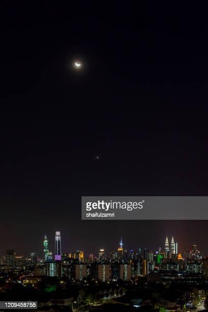 night view over downtown kuala lumpur with crescent moon and venus as part of the night. - shaifulzamri - fotografias e filmes do acervo