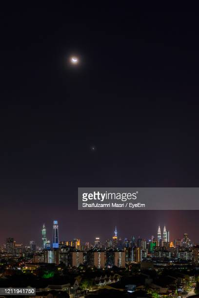 night view over downtown kuala lumpur with crescent moon and venus as part of the night. - shaifulzamri stock-fotos und bilder