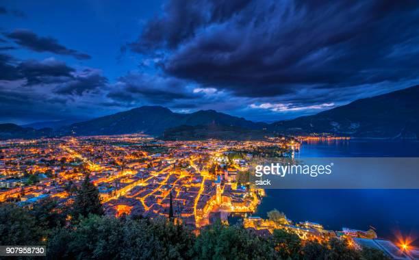 night view over riva del garda and the lake garda - trento foto e immagini stock