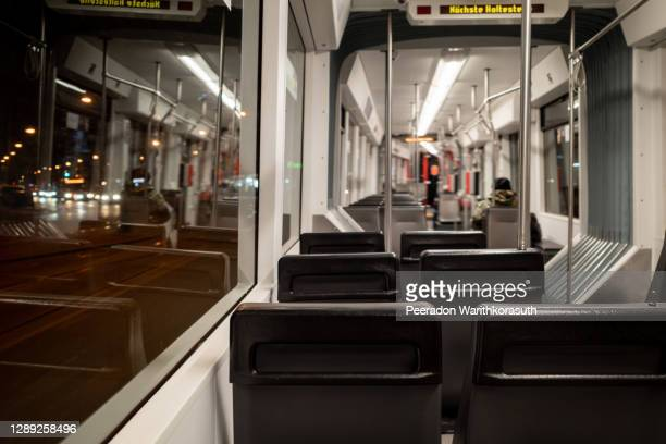 night view selective focus view at empty seat on the light rail tram and blur background of passengers wear face mask protection during epidemic of covid-19 in düsseldorf, germany. - tram stockfoto's en -beelden