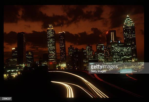A night view shows the skyline of Atlanta Georgia the site of the 1996 Olympic Games with the freeway in the foreground