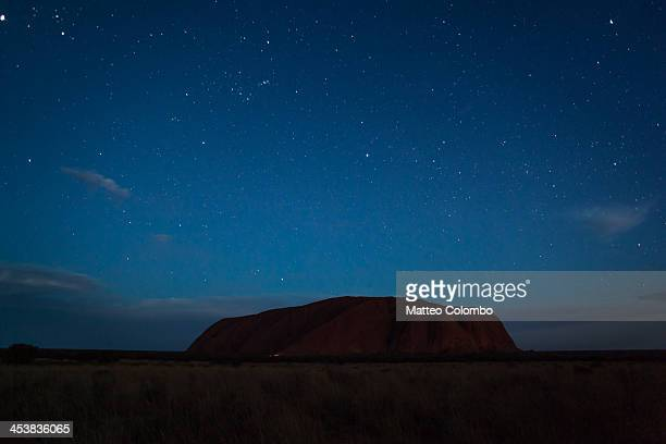 Night with clear starry sky over Uluru, in the red sand desert of Northern Territory, Australia. Uluru, also known as Ayers Rock, is a large...