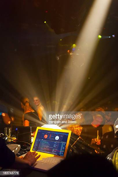 Nightclub scene with people dancing, disc jockey mixing desk with computer