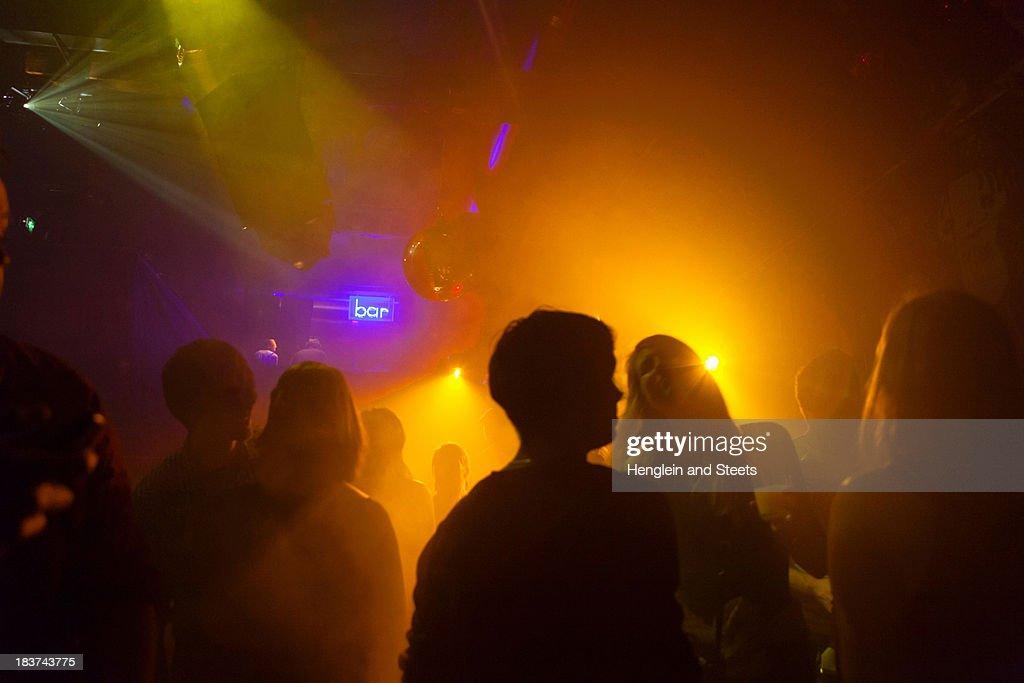 Nightclub scene with people dancing, disco ball, lighting equipment : Stock Photo
