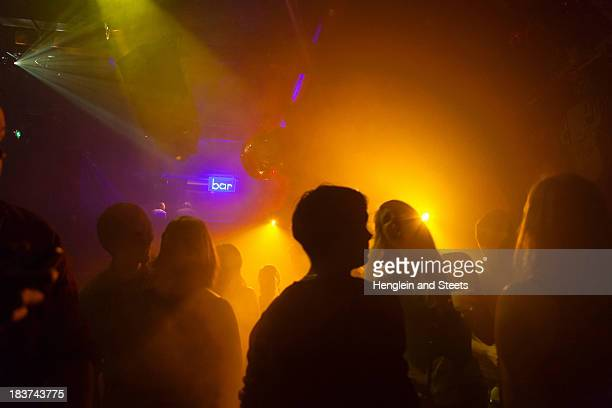 Nightclub scene with people dancing, disco ball, lighting equipment