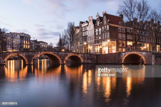nightfall over the idyllic canals of amsterdam old town in the netherlands - amsterdam stock pictures, royalty-free photos & images