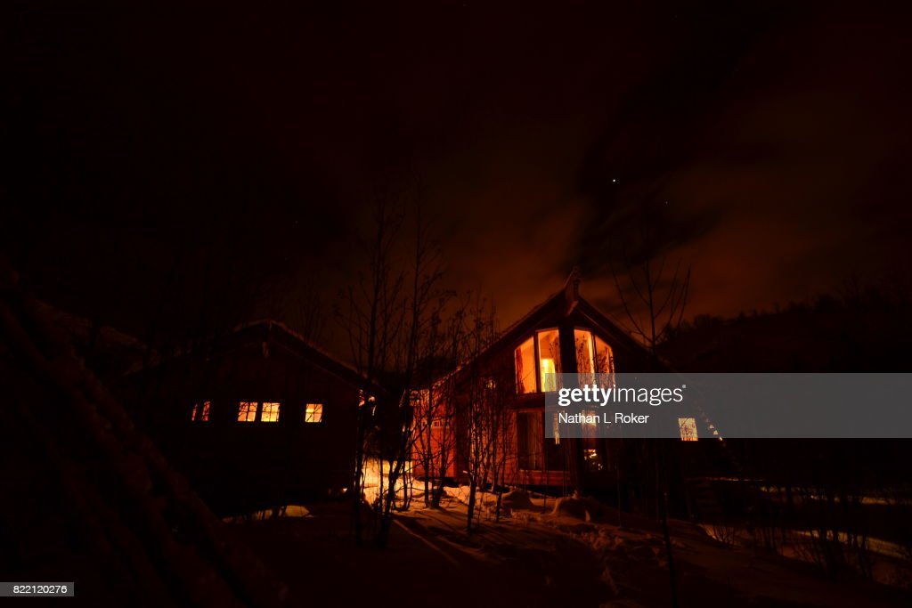 A nightime view of Norwegian cabin retreats, surrounded by snow. : Stock Photo