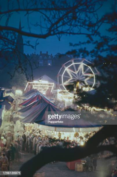 Nightime view of visitors enjoying attractions a Ferris wheel wall of death and fairground rides at a travelling funfair in Chester England in 1956