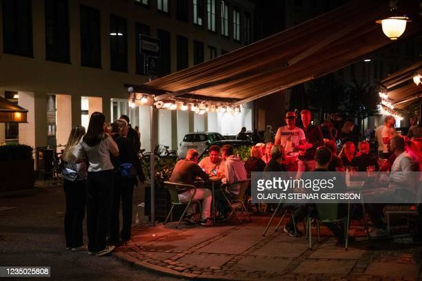 """Nightlife guests are seen at the """"Det Elektriske Hjoerne"""" bar in Copenhagen during the night between September 2 and 3 as Denmark lifted restrictions..."""