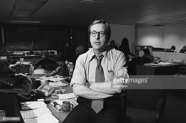 Nightly News anchorman John Chancellor sits on a desk in the NBC newsroom.
