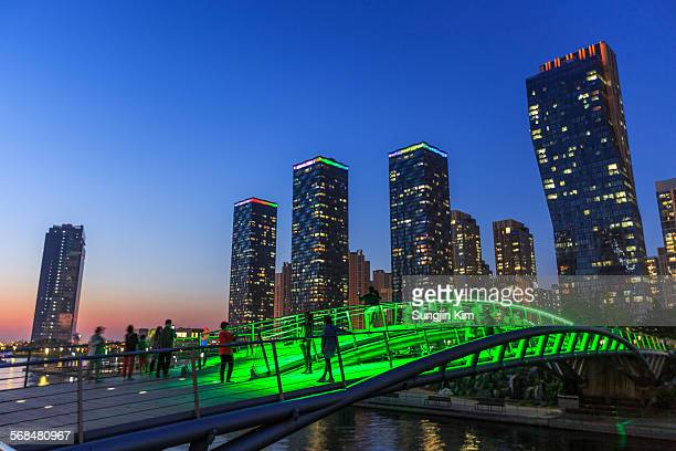 nightscape of high rise buildings and bridge - songdo ibd stock pictures, royalty-free photos & images