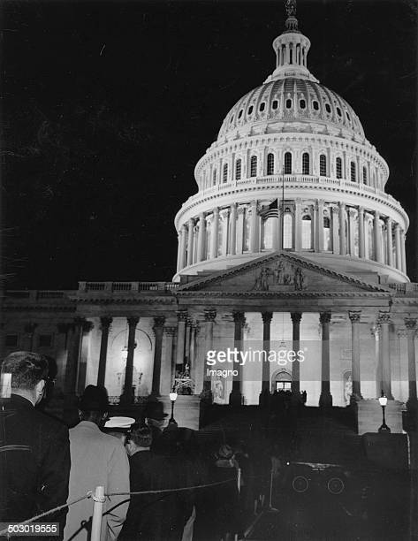 Nightshot of the Capitol. The flood lighted Capitol Building where President Kennedy's body is lying in state. In the foreground are still people in...