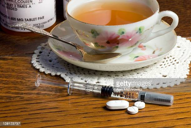 nightstand displaying various ms medications along with cup of tea. the syringe is a dosage of rebif. a one month supply of rebif can cost anywhere from $1,600 to more than $2,000 usd. rebif is a disease-modifying drug (dmd) used to treat multiple sclerosi - multiple sclerosis stock photos and pictures