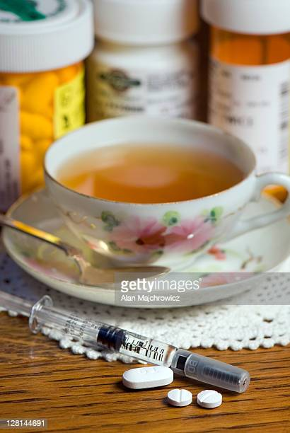 nightstand displaying various ms medications along with cup of tea. the syringe is a dosage of rebif. a one month supply of rebif can cost anywhere from $1,600 to more than $2,000 usd. rebif is a disease-modifying drug (dmd) used to treat multiple sclerosi - 2000 2009 stock pictures, royalty-free photos & images