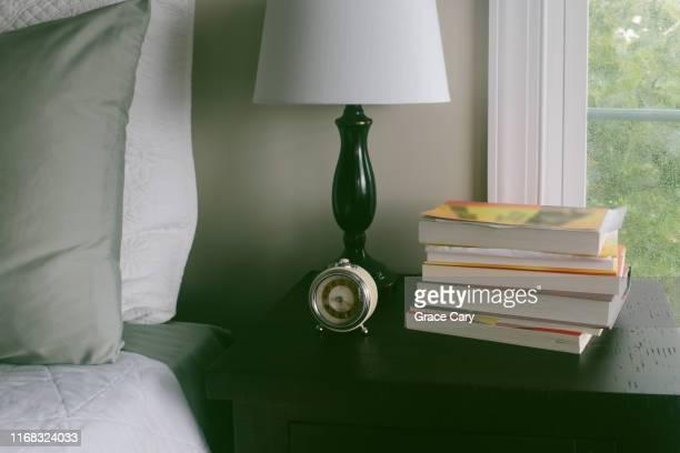nightstand with pile of books - シリーズ画像 ストックフォトと画像