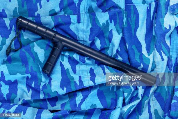 nightstick on blue camouflage clothing - truncheon stock pictures, royalty-free photos & images